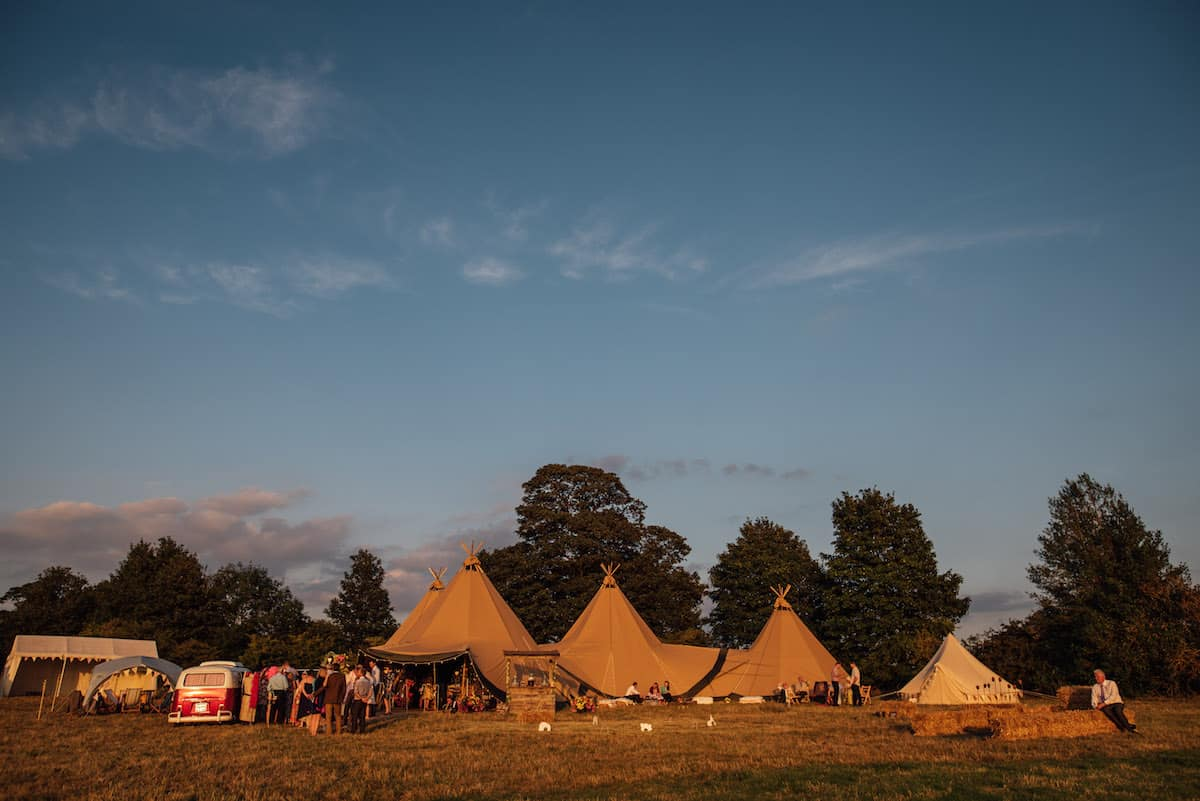 Three giant hat teepees and chill-out tipi at dusk