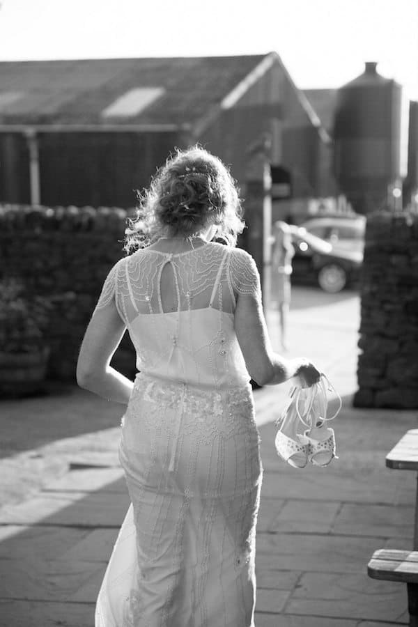 Siobhan walking to wedding holding shoes