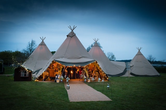Sami Tipi at dusk - Three giant hat tipis in a triangle with chill-out tipi
