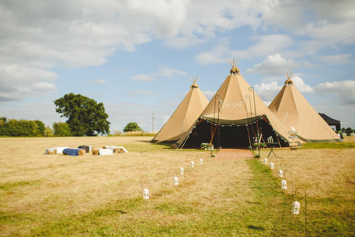 Three giant hat tipis with lantern walkway - Sami Tipi Wedding Captured by Camera Hannah