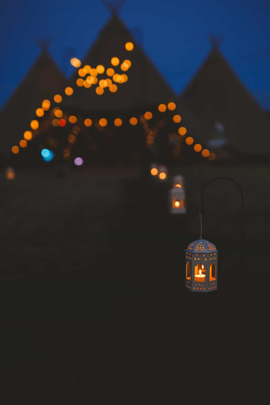 festoon and lantern light tipi walkway at night