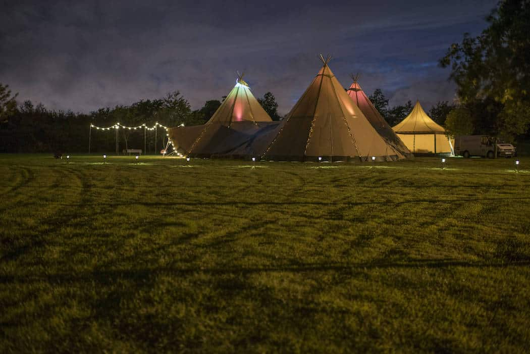 3 Giant hat tipis by night - Victoria and Adams Sami Tipi Wedding at Bawdon Lodge Farm, Captured by Thomas & Thomas