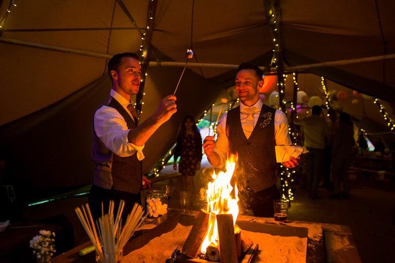 Groomsmen enjoying toasting marshmallows over the open fire