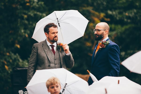 Wet wedding ceremony at bradgate park - wedding party making the most if it with umbrellas