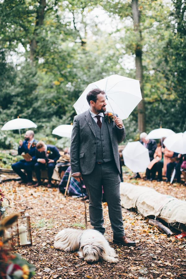 Wet wedding ceremony at bradgate park - groom making the most if it with an umbrella in hand