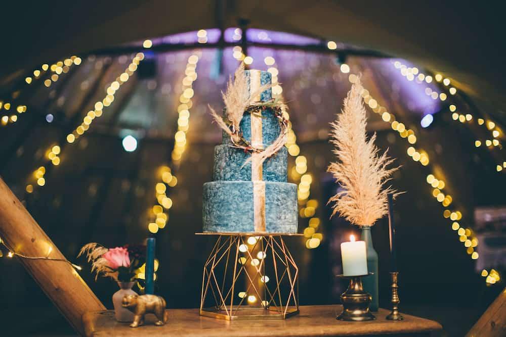 Boho styled wedding cake surrounded by tipi fairy lights at night
