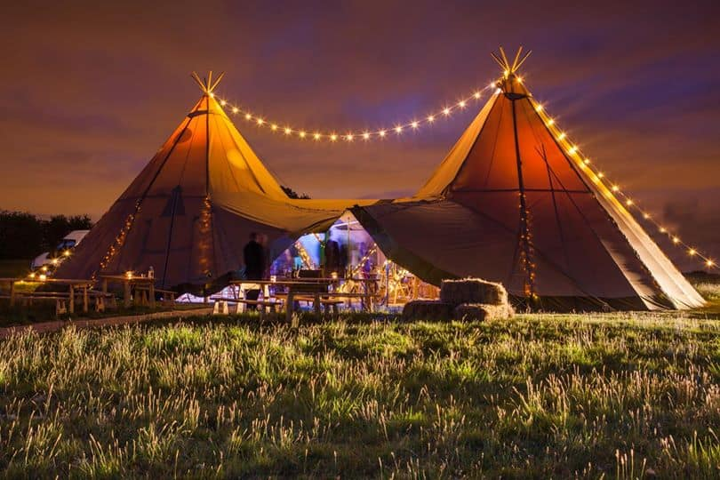 Festoon Lighting over the top of the Tipis. A perfect way to light your evening sky and add extra wow to your celebration tipis. A photographers dream too! Image captured of Sami Tipi wedding by Chris Terry Photography