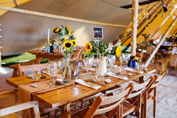 Teepee wedding at Cuttle Brook with bright sunflowers and beach themed table names