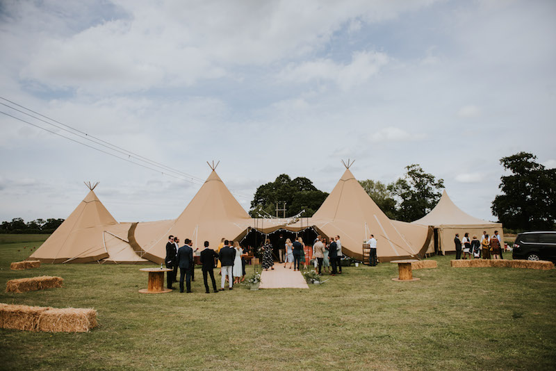 Guests Arriving at The Two giant hats and chill-out tipi wedding celebration at Cuttle Brook. This waterfront wedding venue offers a relaxed wedding setting.