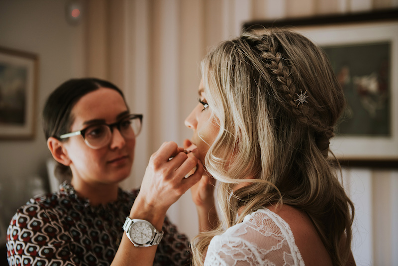 Bride getting ready finishing touches by makeup artist