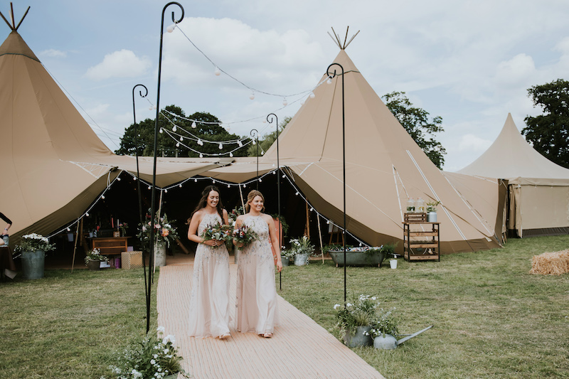 Bridesmaids wearing asos dresses with gorgeous florals walking down Tipi Walkway to the outdoor ceremony. Ceremony held at Cuttle Brook, a waterfront wedding venue in Derbyshire