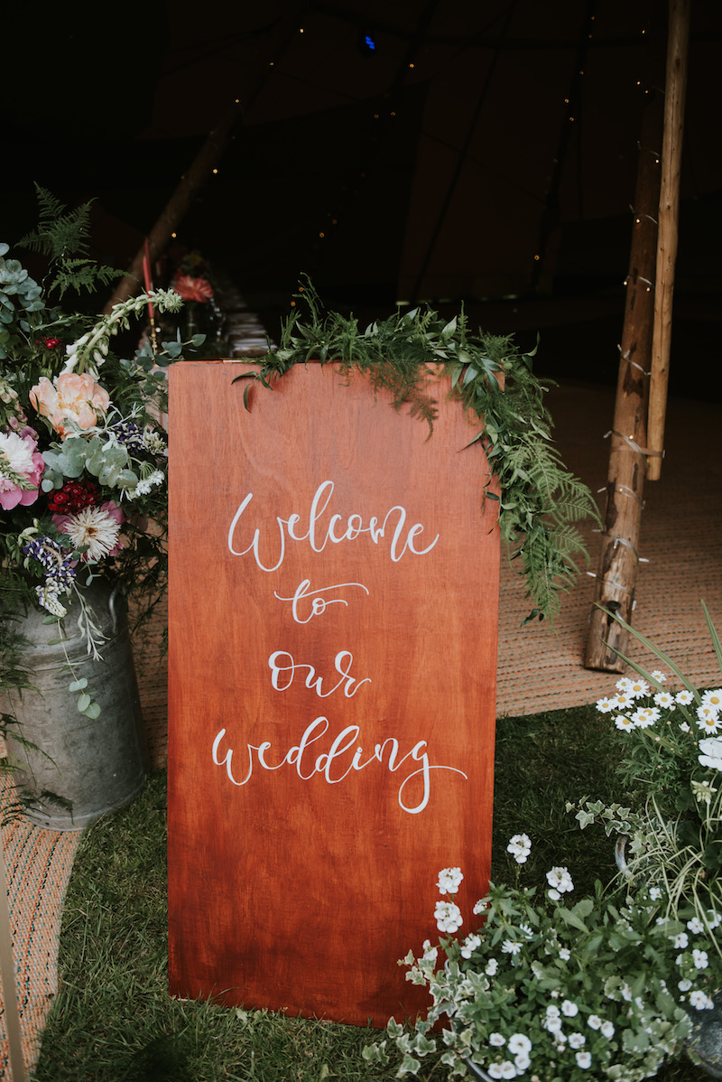 welcome to our wedding sign complete with florals