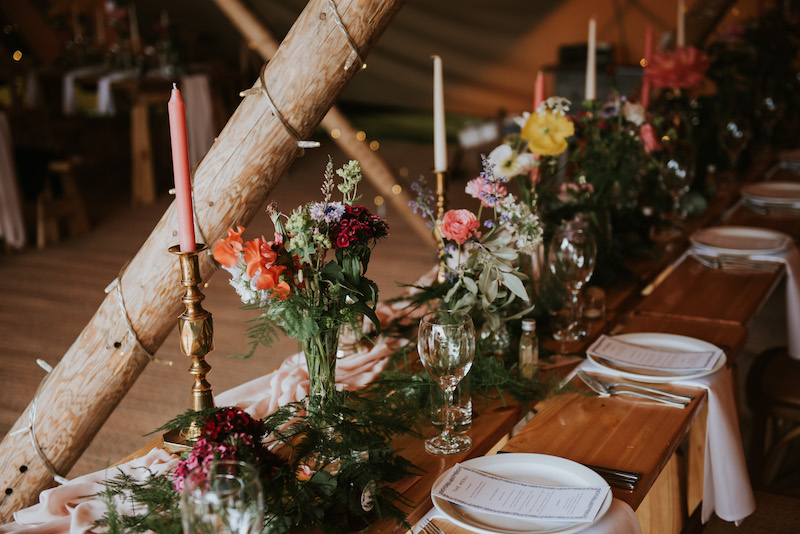 Tipi Table setup with florals, plates and menus