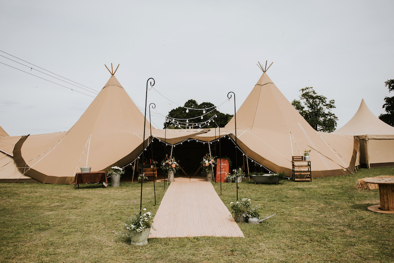 2 giant hats and chill out tipi Tipi entrance with florals and festoon walkway