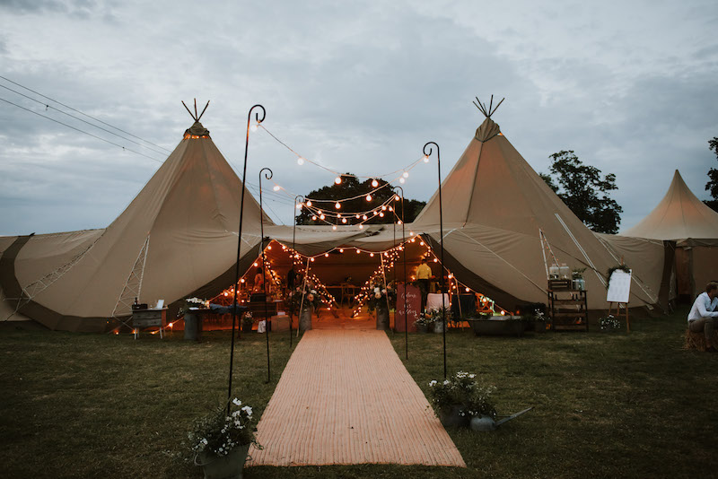 tipis at dusk. As the light changes and festoon walkway and fairy lights begin to glow
