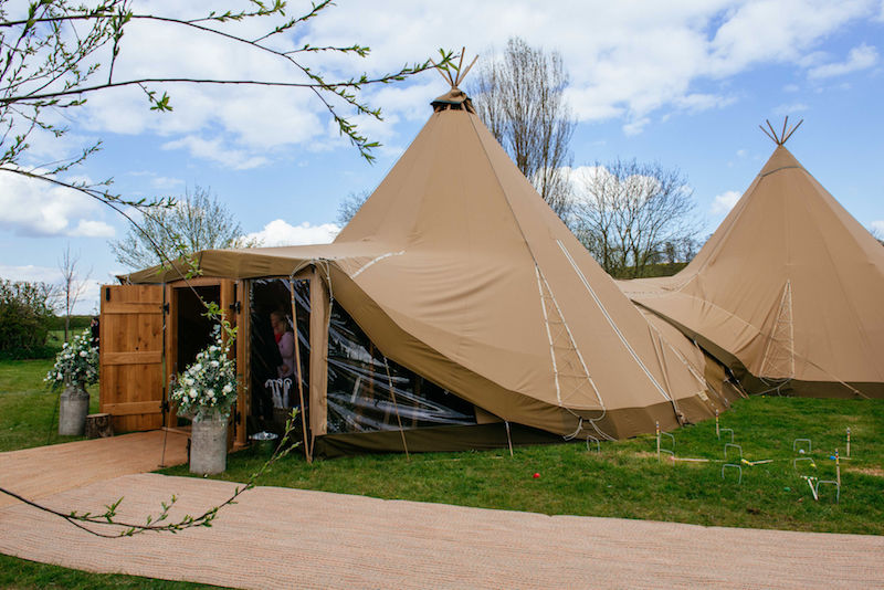 Spring Tipi Wedding Setup complete with wooden doors and clear frontage