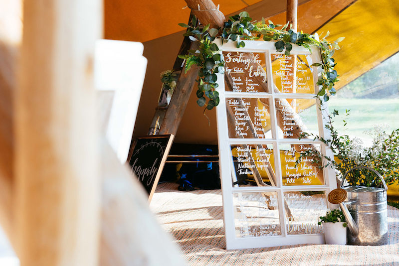 Glazed window seating plan for Spring Tipi wedding complete with greenery