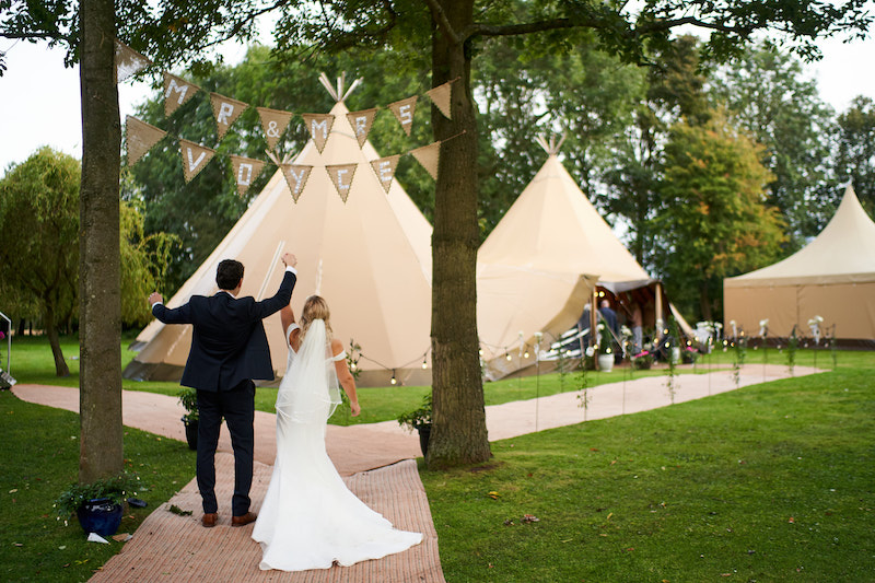 Happy couple in front of tipis