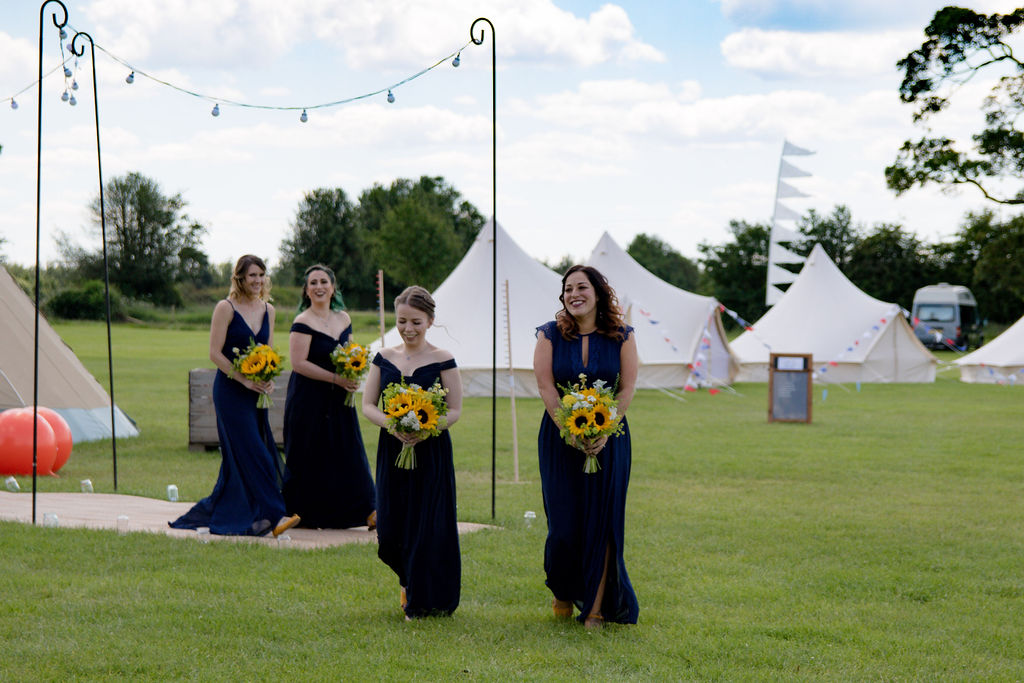 Cattows farm wedding 8 Bridesmaids wearing Navy with sunflower bouquets walking to ceremony