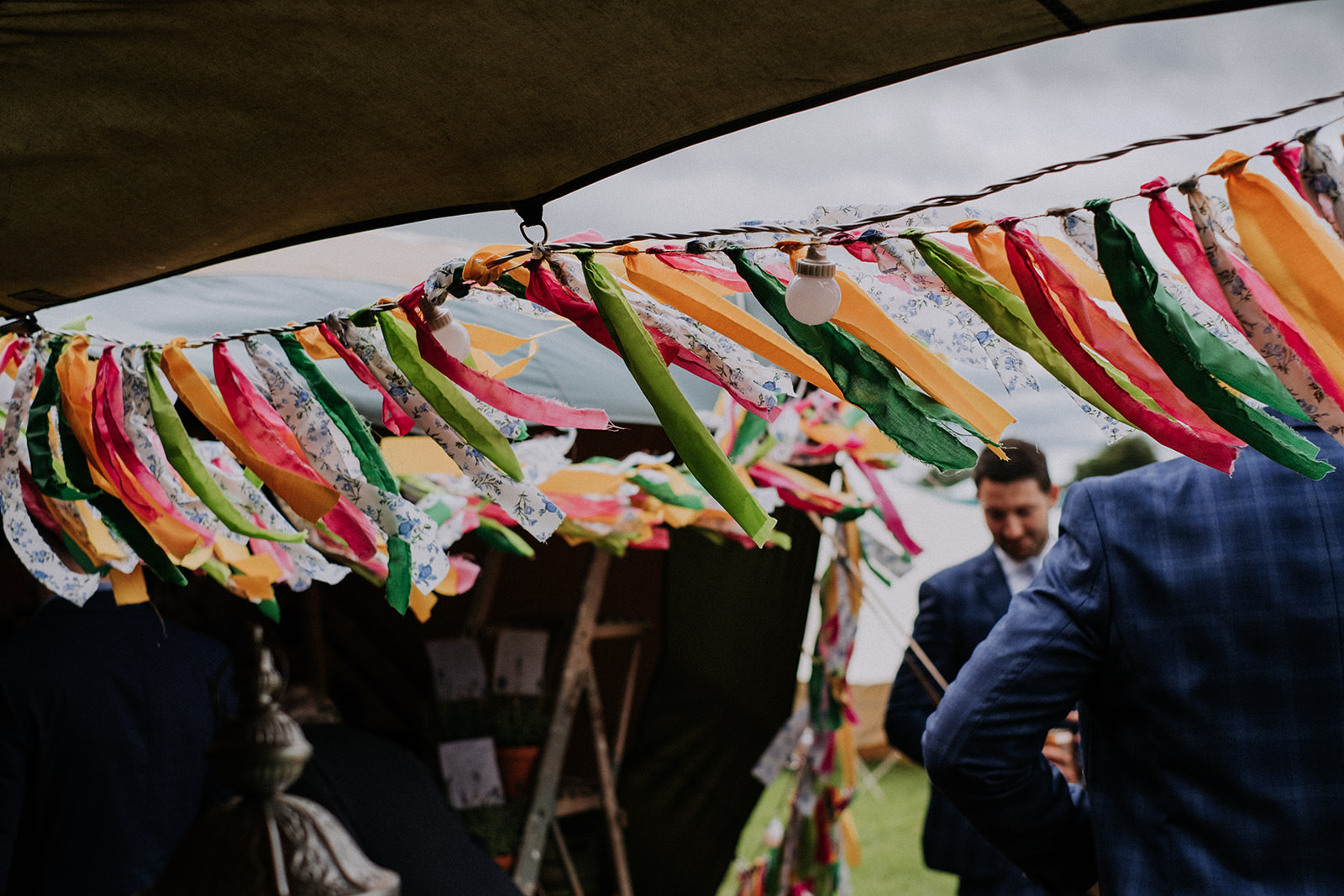 Colourful rag bunting on tipi entrance. Cattows farm wedding with sami tipi