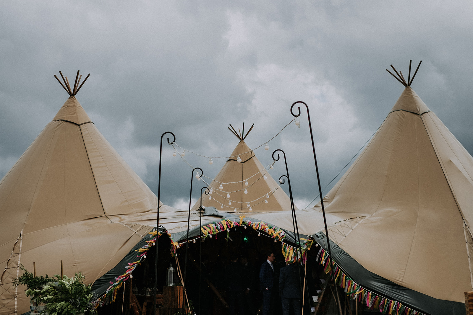 tipi wedding entrance covered in colourful rag bunting - cattows farm wedding with sami tipi