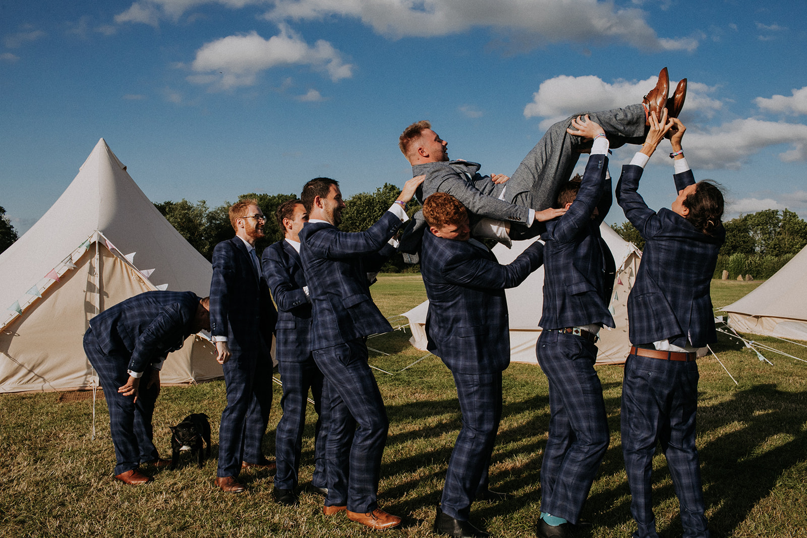 groom being carried by groomsmen - cattows farm wedding with sami tipi