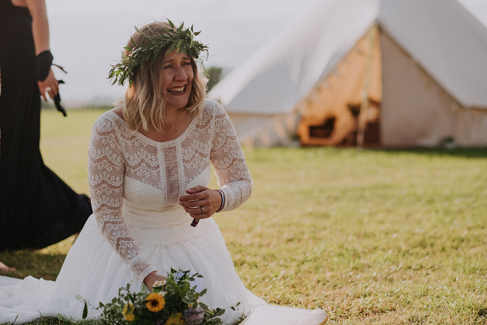 Bride enjoying her day, laughing at groom being carried - cattows farm wedding with sami tipi