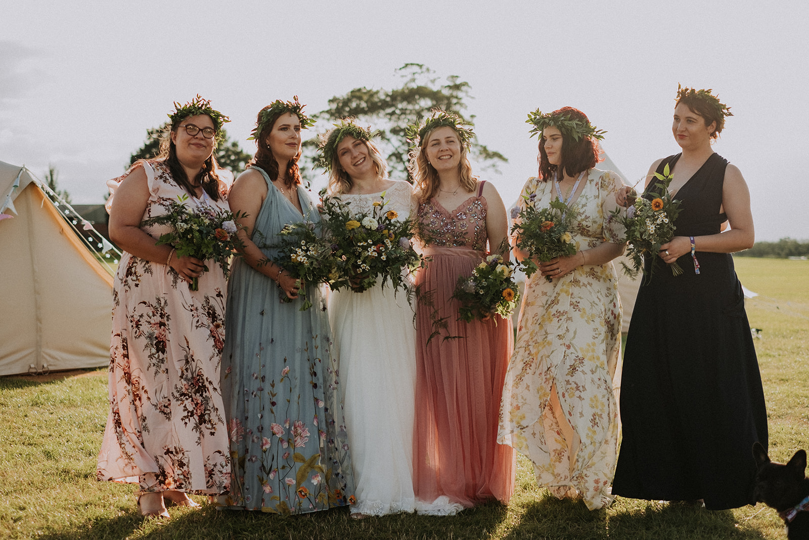 Bride and bridesmaids wearing all different dresses for cattows farm wedding