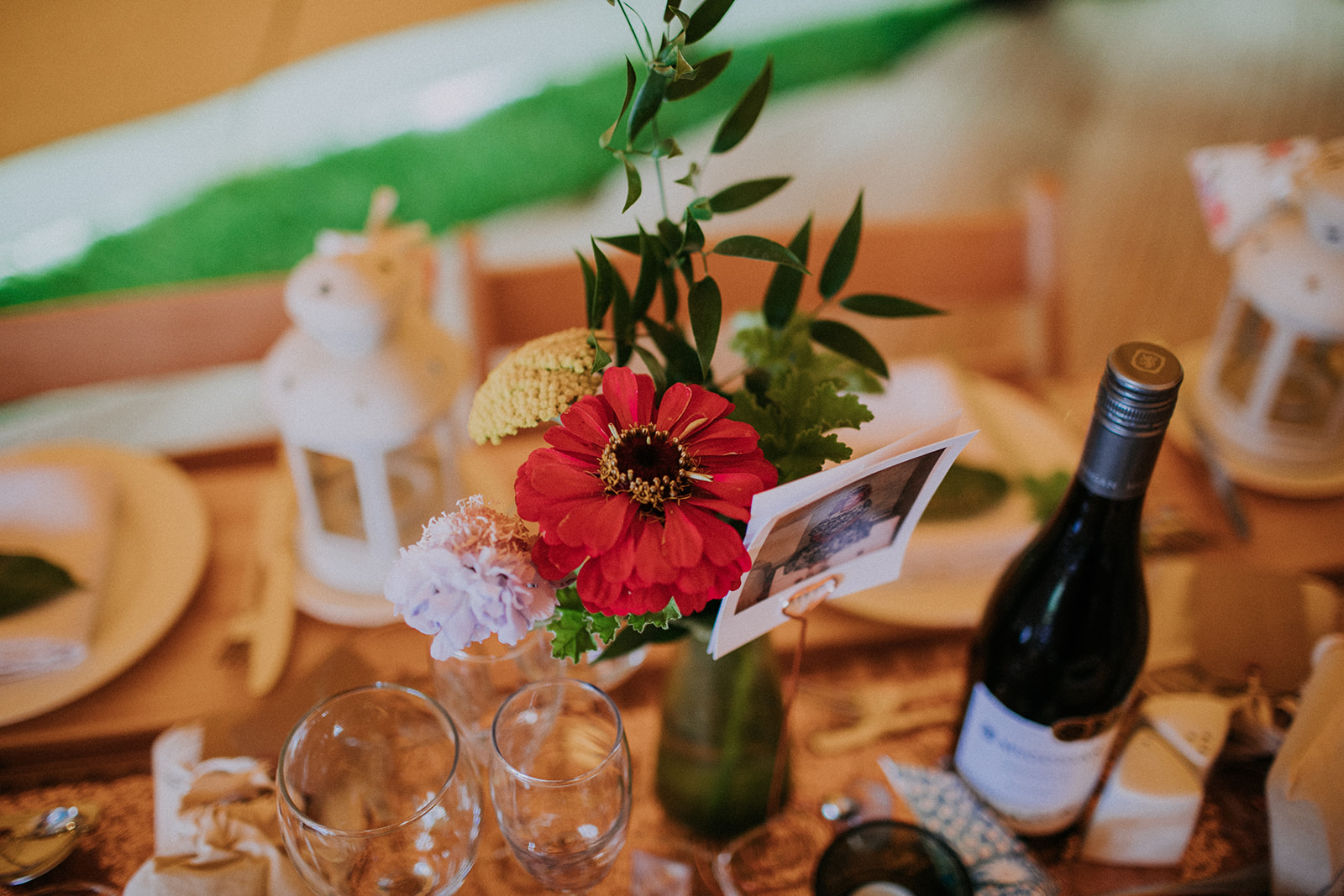 Table details with flowers and photos for cattows farm wedding with sami tipi