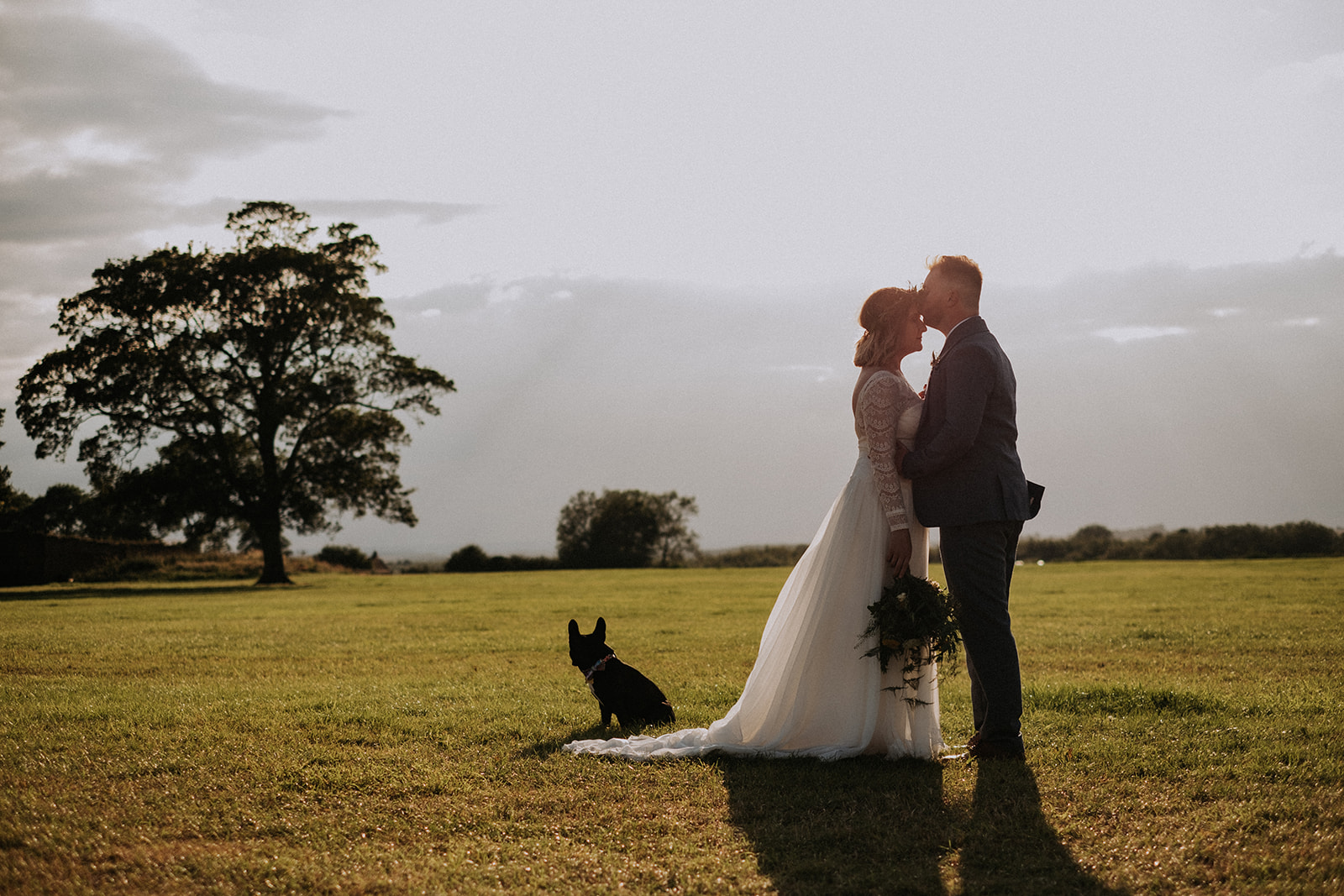 Cattows Farm Wedding with bride and groom enjoying a walk around the farm with the family dog