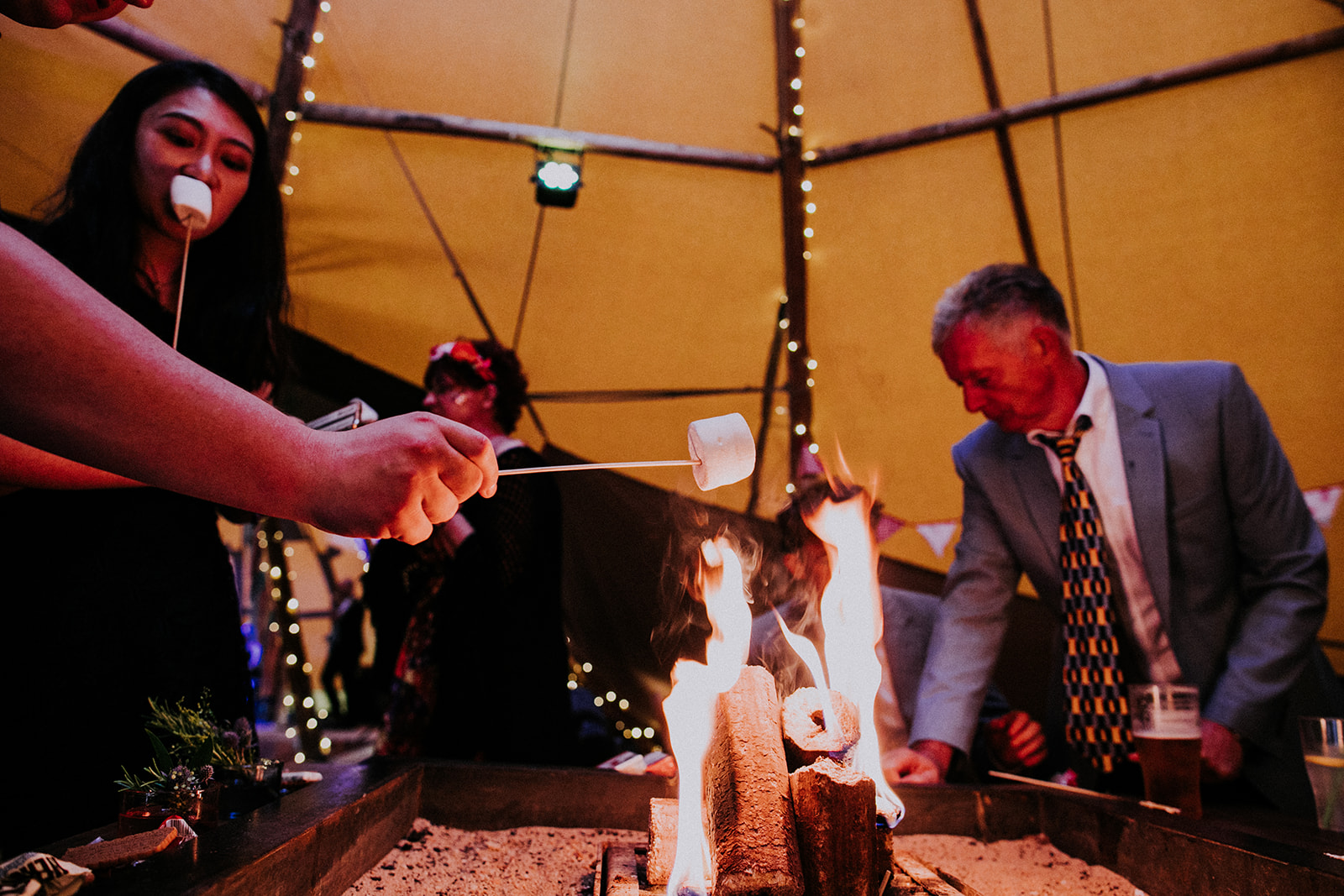 toasting marshmallows at teepee wedding cattows farm wedding with sami tipi