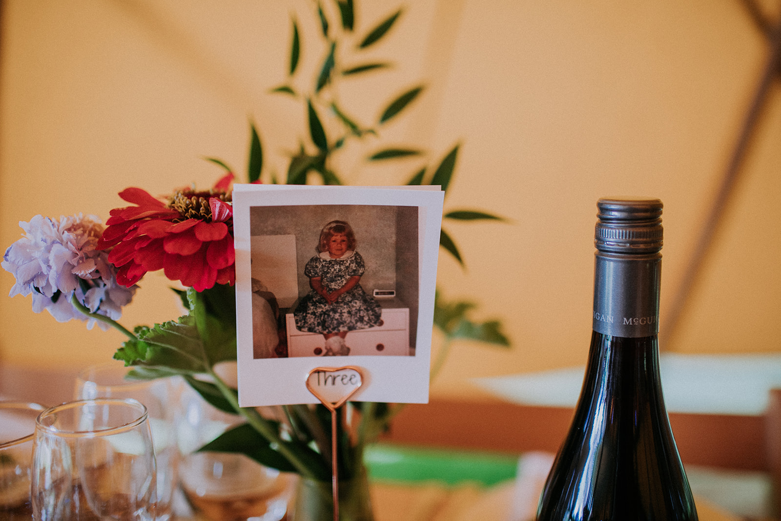 Table Three complimented with photo of bride and groom aged 3. Cattows farm wedding with sami tipi