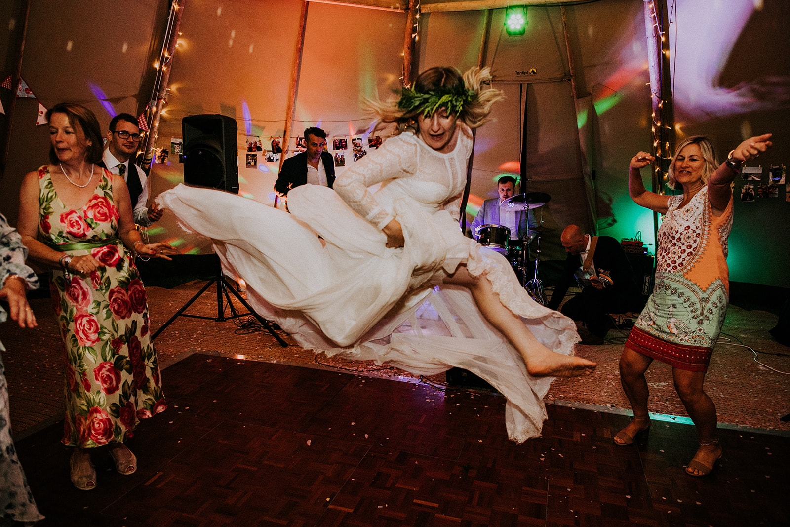Bride doing jump in the middle of the dance floor
