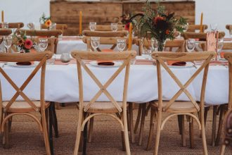 Long tables with cloths and cross back chairs in Sailcloth Tent