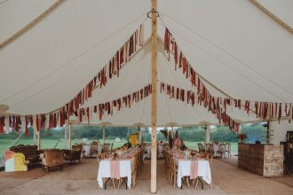 Internal view from the dance floor of a two pole sailcloth tent with vintage furniture set, rag bunting and rustic bar