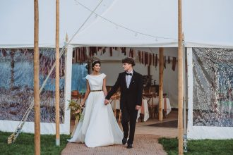 Sailcloth Tent entrance with Festoon Walkway and bride and groom walking under