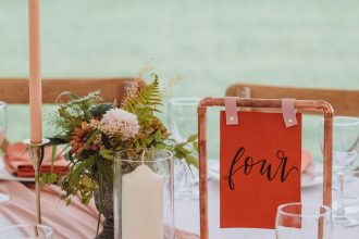 Copper and leather table names with hand lettering in Sailcloth Tent