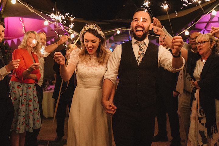 couple enjoying a sparkler send off in front of their tipis