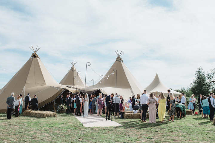 four giant hat tipi wedding exterior, guests mingling at outdoor wedding