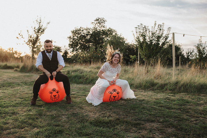 married couple playing on space hoppers, perks of an outdoor wedding