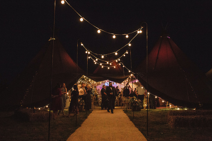 festoon walkway for four giant hat tipis at night